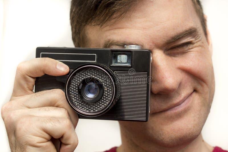 Homme dans un T-shirt rouge avec le vieil appareil-photo photo libre de droits