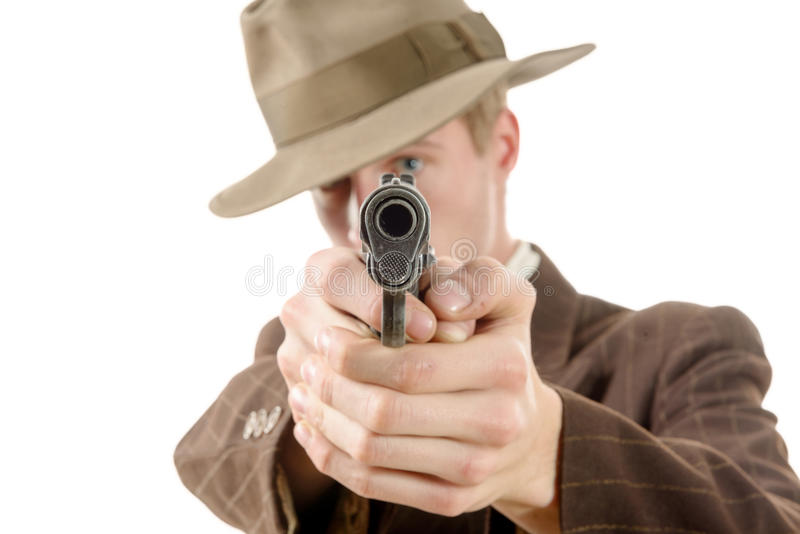 Homme dans un vintage de costume, but avec une arme à feu photographie stock