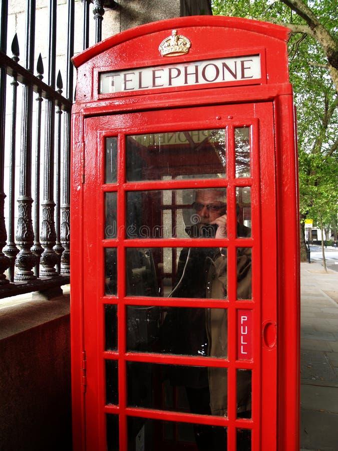 Homme dans une cabine de téléphone rouge, Londres photo libre de droits