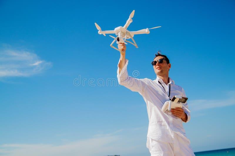 Homme dans une chemise actionnant un bourdon avec à télécommande sur la mer image stock