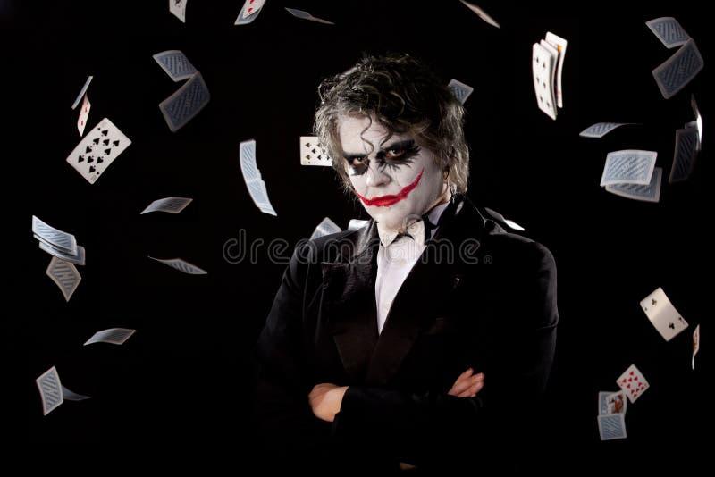 Homme dans une image d'un joker avec des cartes de mouche image stock