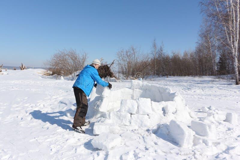 Homme dans une veste bleue construisant un igloo sur une clairière photo stock