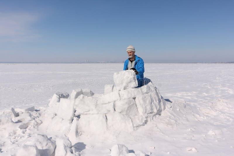 Homme dans une veste bleue construisant un igloo sur une clairière photos stock