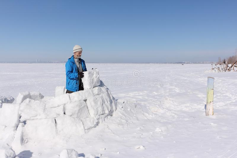 Homme dans une veste bleue construisant un igloo sur une clairière image libre de droits