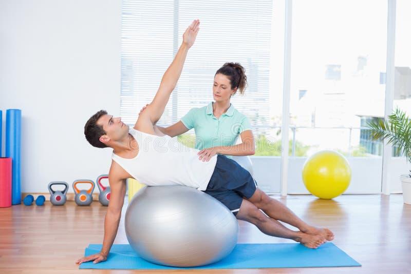 Homme de aide d'entraîneur avec la boule d'exercice photo stock