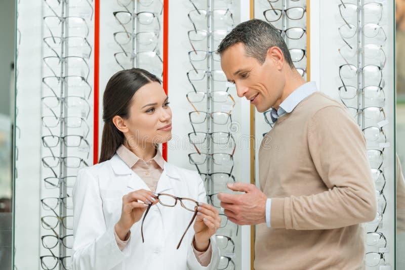 homme de aide d'oculiste pour choisir des paires de lunettes image stock