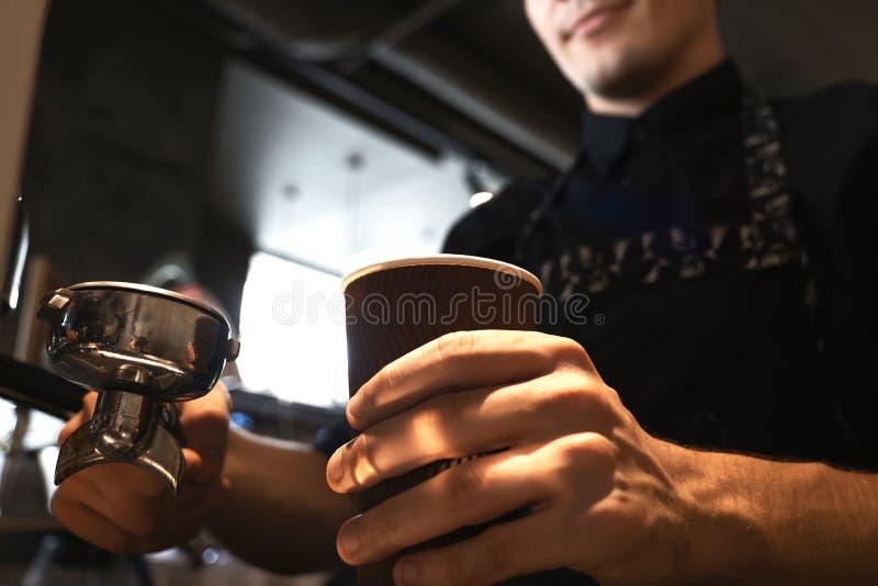 Homme de barman dans le tablier tenant la boisson chaude de café dans la tasse de papier dans un main et support dans des autres  photographie stock libre de droits