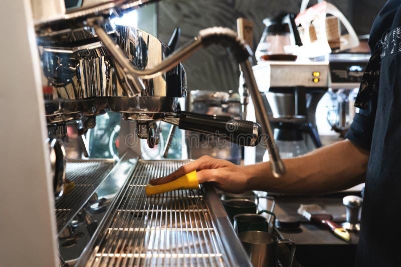 Homme de barman essuyant la machine professionnelle de café avec du chiffon en café photo libre de droits