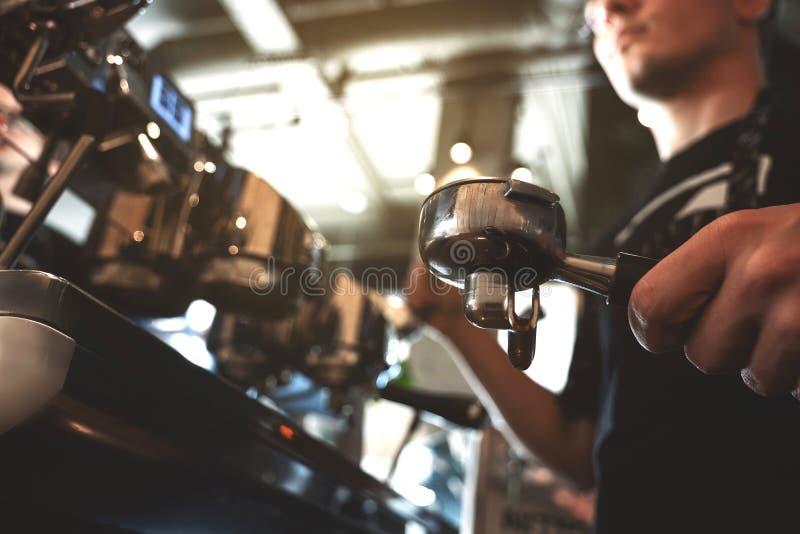 Homme de barman tenant le support de café avec le cafè moulu dans une position de main près de la préparation professionnelle de  image stock