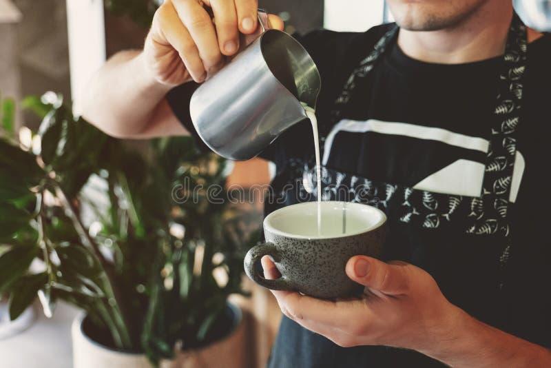 Homme de barman versant le lait fouetté de mousser le broc dans la tasse avec du café en café photographie stock