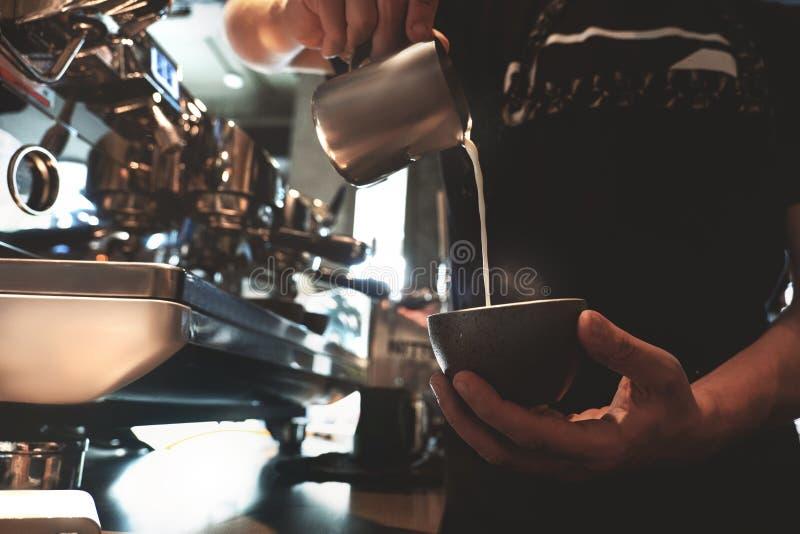 Homme de barman versant le lait fouetté de mousser le broc dans la tasse avec du café se tenant devant le café professionnel images libres de droits