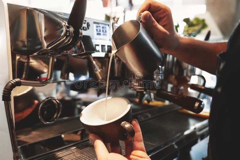Homme de barman versant le lait fouetté de mousser le broc dans la tasse avec du café se tenant près de la machine professionnell image libre de droits
