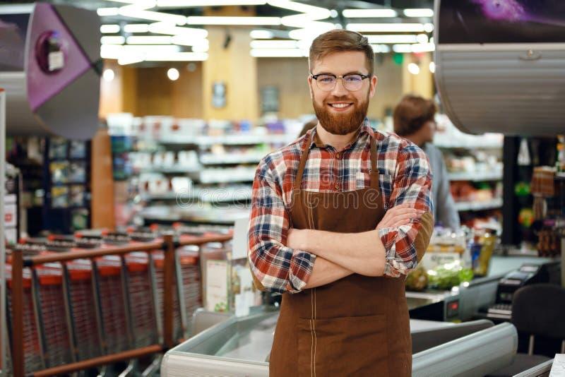 Homme de caissier sur l'espace de travail dans la boutique de supermarché photos libres de droits