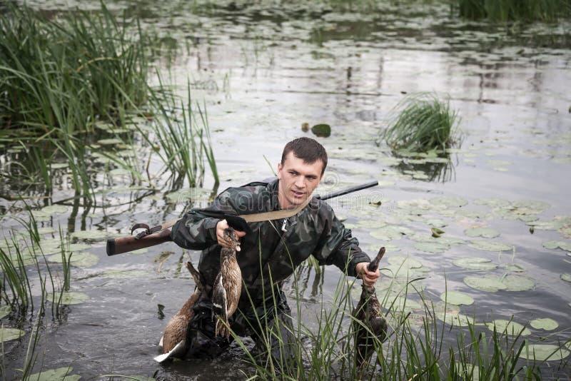 Homme de chasseur avec la proie après une interruption réussie de chasse par le marécage images libres de droits
