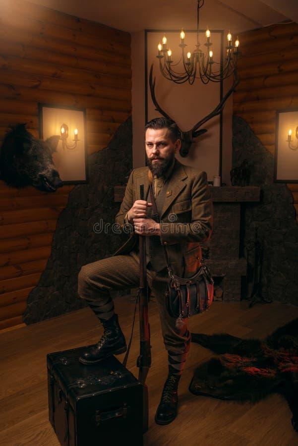Homme de chasseur avec la vieille arme à feu contre le coffre antique photo libre de droits