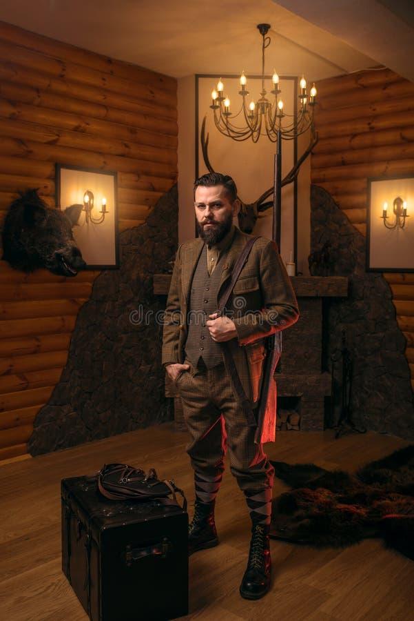 Homme de chasseur avec la vieille arme à feu contre le coffre antique image libre de droits