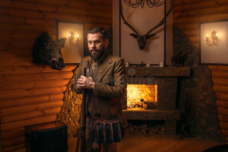Homme de chasseur avec la vieille arme à feu contre le coffre antique photographie stock libre de droits