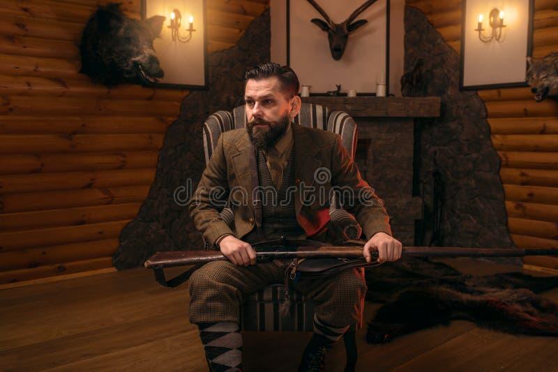 Homme de chasseur avec la vieille arme à feu contre le coffre antique photo stock
