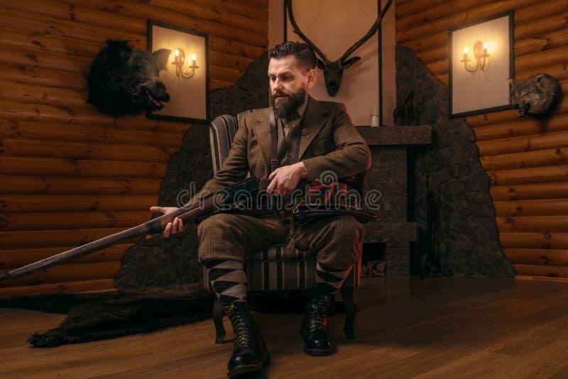 Homme de chasseur dans l'habillement de vintage avec le fusil antique photographie stock