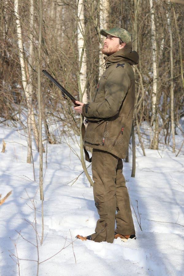 Homme de chasseur dans l'habillement kaki foncé dans la forêt image libre de droits