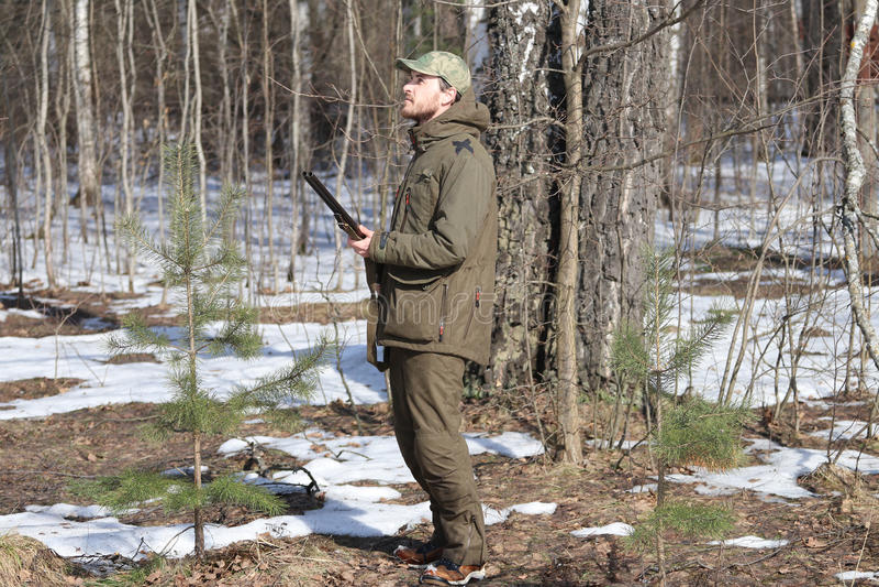 Homme de chasseur dans l'habillement kaki foncé dans la forêt photo stock