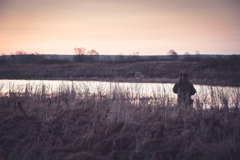 Homme de chasseur dans le domaine rural dans l'attente de la chasse pendant le lever de soleil avec l'espace de copie images stock
