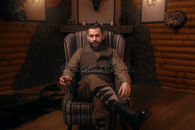 Homme de chasseur s'asseyant dans un whiskey de chaise et de boissons images libres de droits