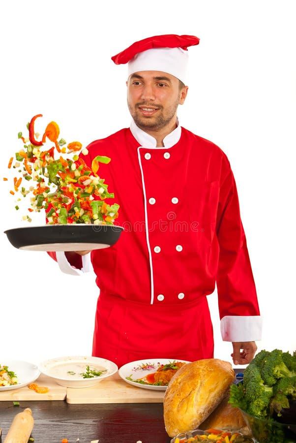Homme de chef jetant des légumes en l'air photos stock