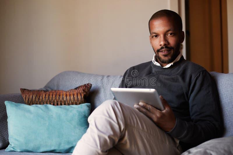 Homme de couleur africain bel à l'aide du comprimé sur le divan de sofa dans le salon à la maison image stock