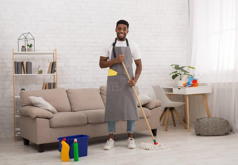 Homme de couleur avec le plancher de nettoyage de balai à la maison images stock