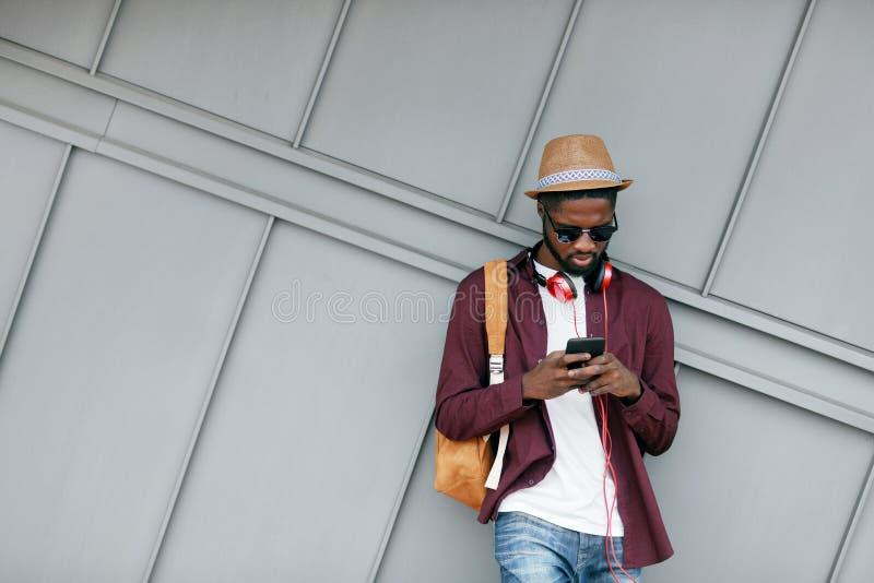 Homme de couleur bel dans des vêtements de mode avec le téléphone sur la rue image stock