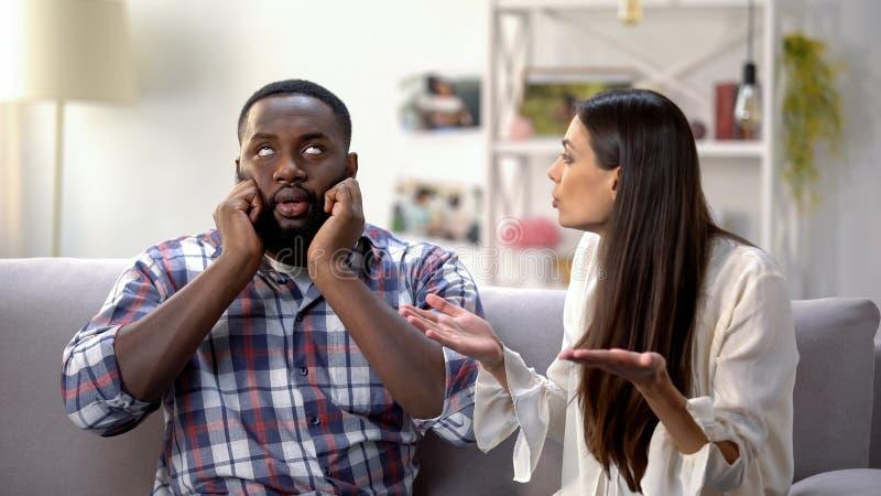 Homme de couleur contrarié ignorant la conversation avec l'amie, malentendu images stock