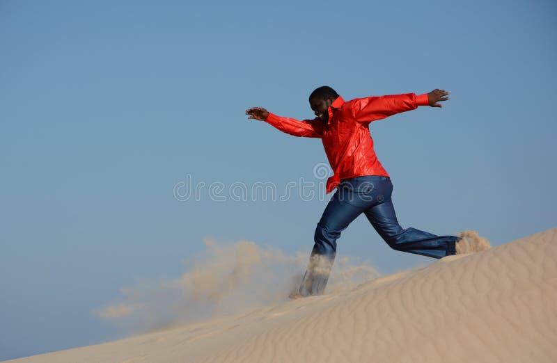Homme de couleur courant en bas de la dune photographie stock