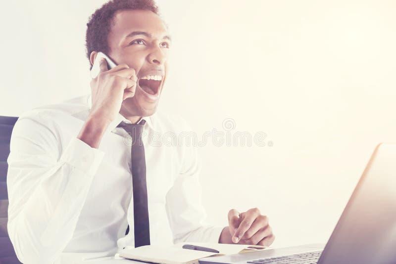 Homme de couleur criant au téléphone portable photographie stock