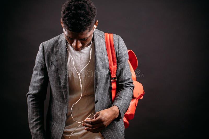 Homme de couleur dans le manteau et le T-shirt s'inquiétant le bagpack rose et choisissant la musique photo stock
