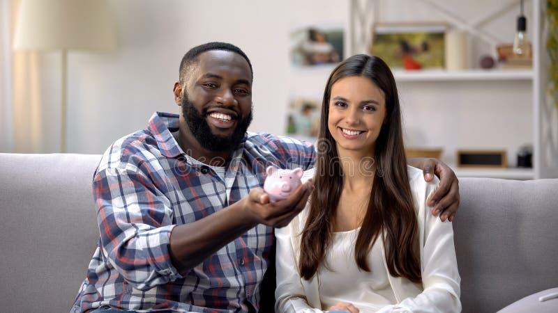 Homme de couleur et jolie femme tenant la tirelire, programme social pour de jeunes familles photo stock