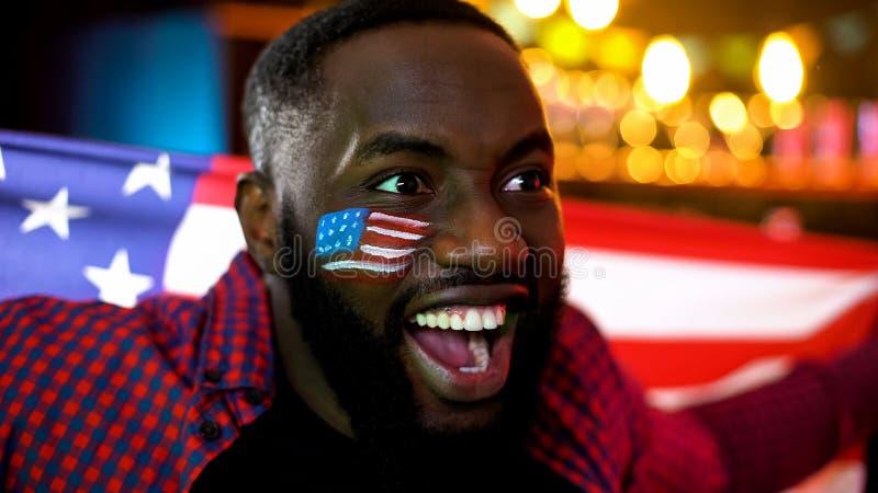 Homme de couleur extrêmement heureux avec le drapeau des Etats-Unis sur l'équipe de sports de soutien de sourire de joue photo stock