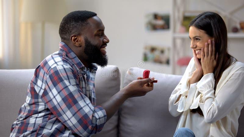 Homme de couleur faisant la proposition à l'amie émotive heureuse, bague de fiançailles, amour images libres de droits