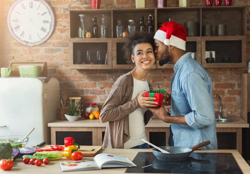 Homme de couleur heureux étonnant son épouse avec le cadeau dans la cuisine image libre de droits