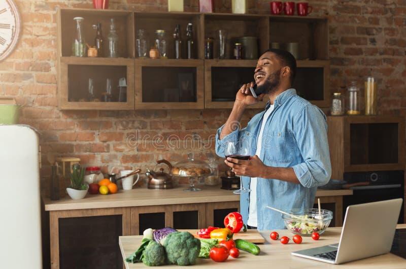 Homme de couleur heureux parlant sur le téléphone et le vin potable images stock