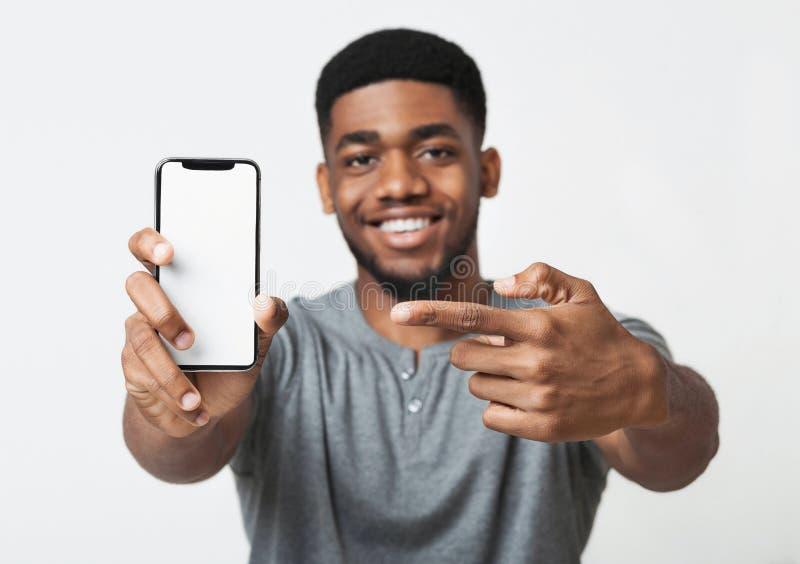 Homme de couleur heureux tenant le dernier smartphone mince photos stock