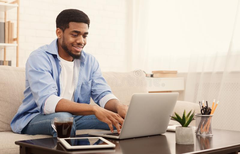 Homme de couleur millénaire travaillant sur l'ordinateur portable dans le siège social photographie stock libre de droits