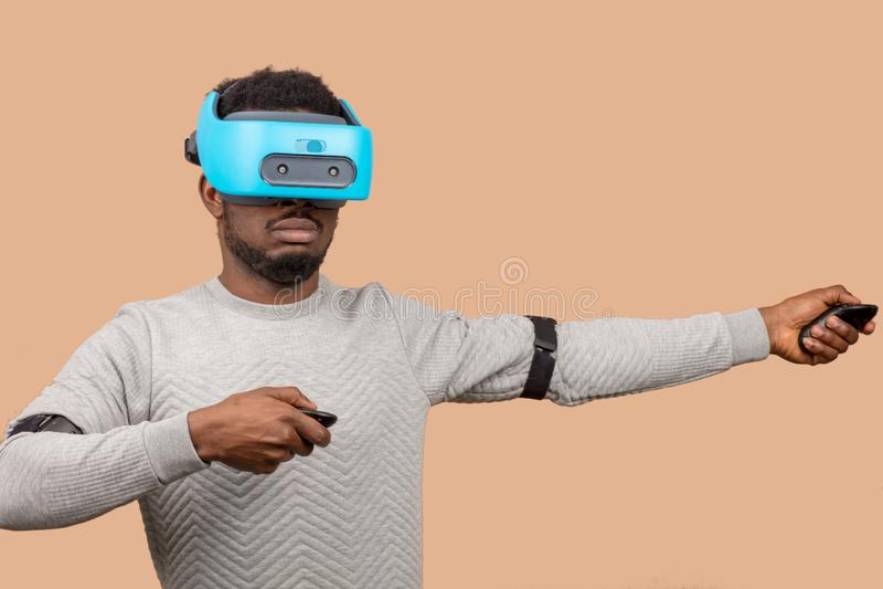 Homme de couleur portant des lunettes du vr 3d, jouant le jeu vidéo, tenant la manette dans des mains images libres de droits