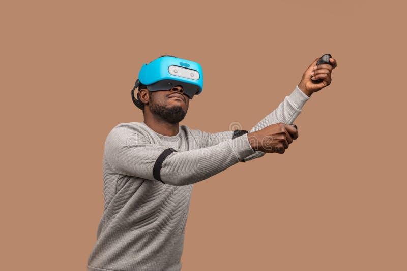 Homme de couleur portant des lunettes du vr 3d, jouant le jeu vidéo, tenant la manette dans des mains photographie stock