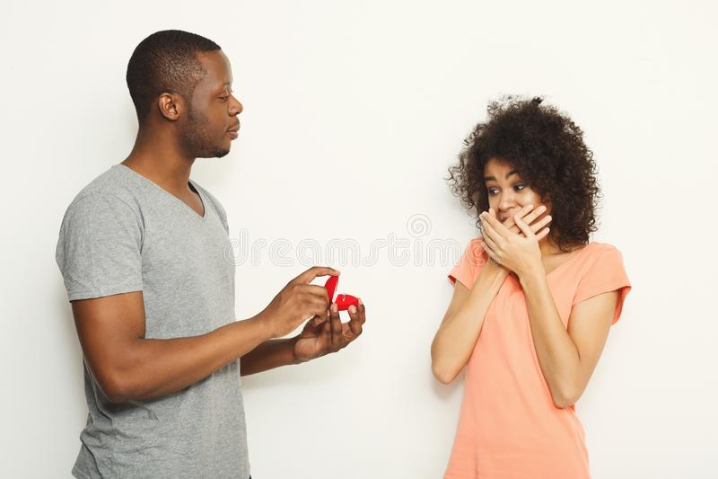 Homme de couleur proposant à son amie choquée photographie stock