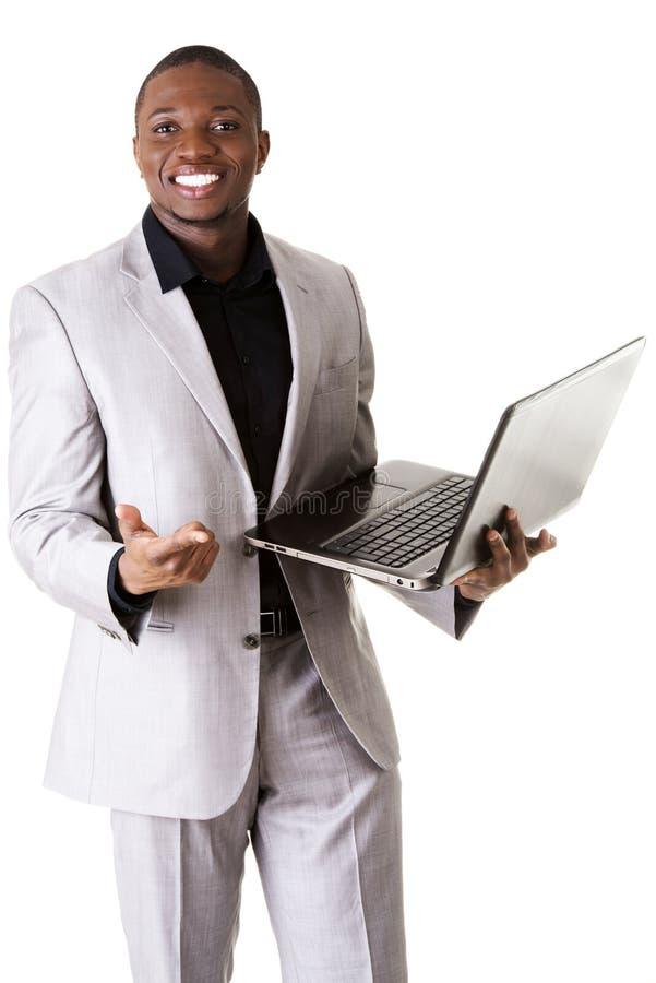 Homme de couleur se tenant avec l'ordinateur portable images stock
