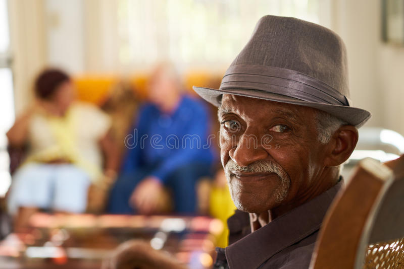 Homme de couleur supérieur avec le chapeau regardant l'appareil-photo dans l'hospice images libres de droits