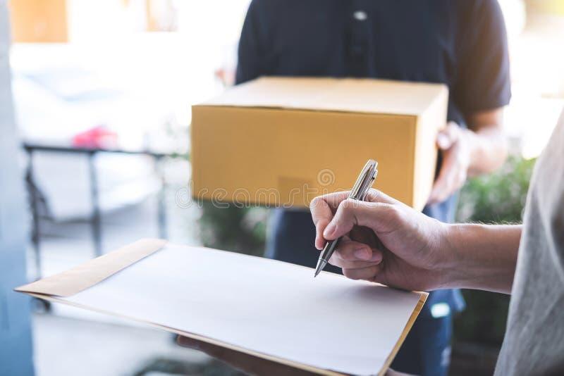 Homme de courrier de la livraison donnant la boîte de colis à la forme de destinataire et de signature, reçu de signature de jeun image libre de droits