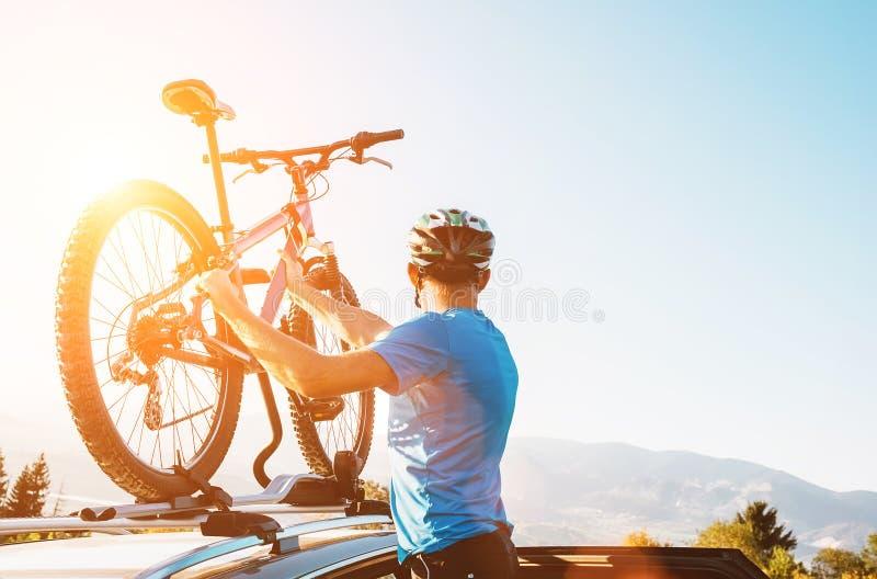 Homme de cycliste de montagne prendre de son vélo du toit de voiture égalisant le su photo stock