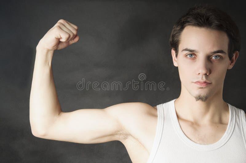 Homme de débutant montrant le sien musculaire image stock